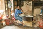 man stirring pot of milk