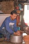 man rinsing clay pots